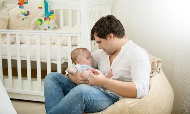Gelukkige vader zit met zijn zoontje op handen in de slaapkamer
