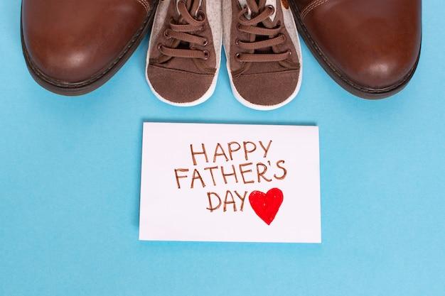 Gelukkige vaderdag met rood hart op een witte pagina en kinder- en vadersschoenen op blauwe achtergrond