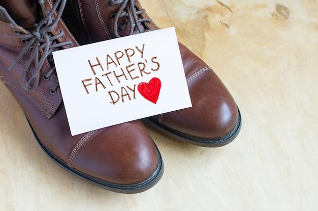 Gelukkige vaderdag op een witte pagina over bruine schoenen die op lichte houten achtergrond worden geïsoleerd