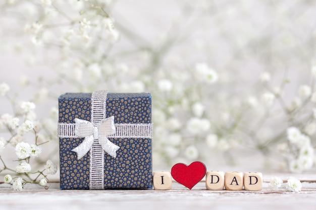 Gelukkige vaderdag. tekst i love dad op achtergrond en geschenkdoos met vervaging gypsophila bloemen. wenskaart voor vakantieconcept.