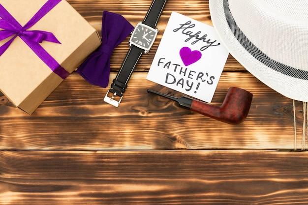 Gelukkige vaderdagkaart met geschenkdoos, stropdas, polshorloge, een hoed en een pijp op houten ondergrond