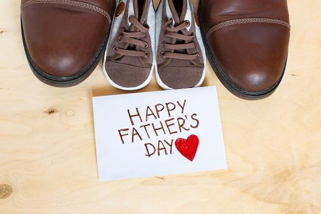 Gelukkige vaderdagkaart met vader en kinderschoenen op lichte houten achtergrond