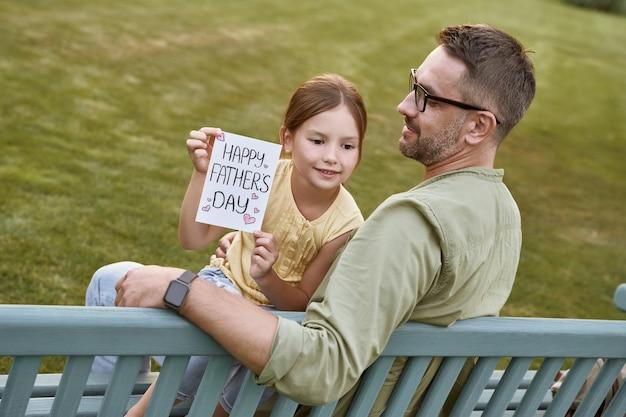 Gelukkige vadersdag vieren buitenshuis jonge liefhebbende vader zittend op de houten bank in park met