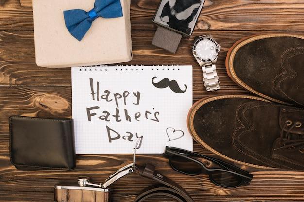 Gelukkige vadersdagtitel op papier dichtbij mannelijke schoenen en toebehoren