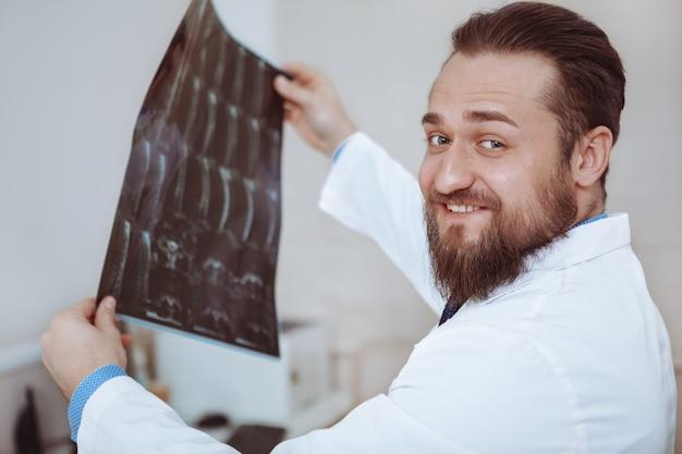 Gelukkige vakman die x-ray scans van een patiënt onderzoekt