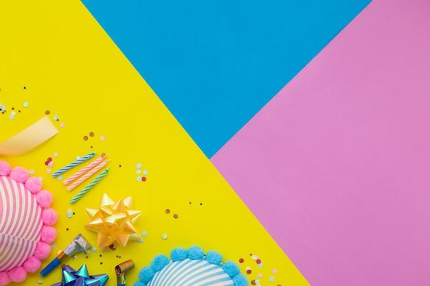Gelukkige verjaardag achtergrond, plat lag kleurrijke feestdecoratie op pastel gele, blauwe en roze geometrische achtergrond.