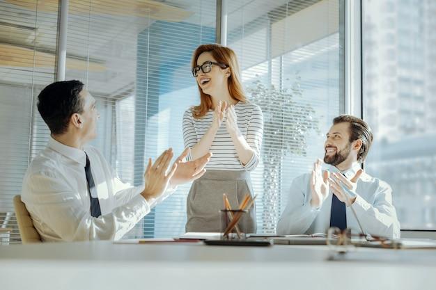 Gelukkige verjaardag. blije prettige collega's die hun baas feliciteren met haar verjaardag en in de handen klappen terwijl de vrouw vrolijk lacht