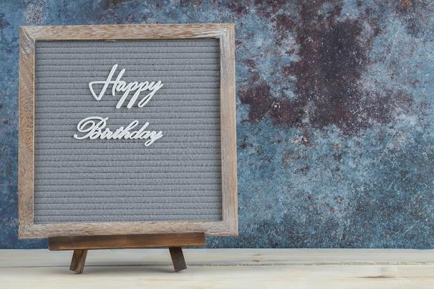 Gelukkige verjaardag die op het houten bureau schrijft
