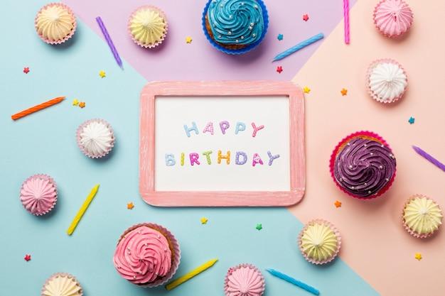 Gelukkige verjaardag geschreven op houten frame omringd met muffins; aalaw; hagelslag en kaarsen op gekleurde achtergrond