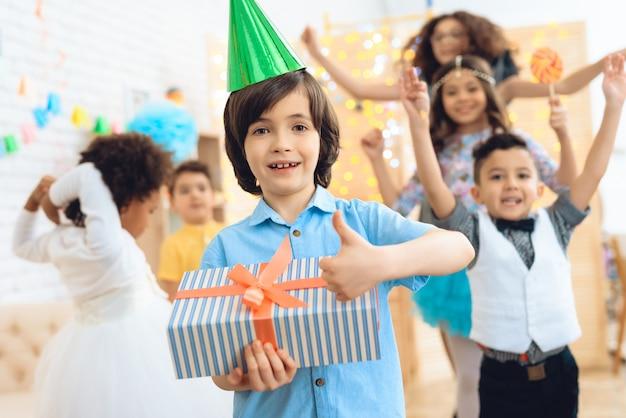 Gelukkige verjaardag jongen in groene feestelijke hoed laat zien dat hij blij is met cadeau.