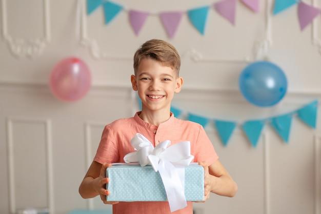 Gelukkige verjaardag jongen met een geschenk in zijn handen
