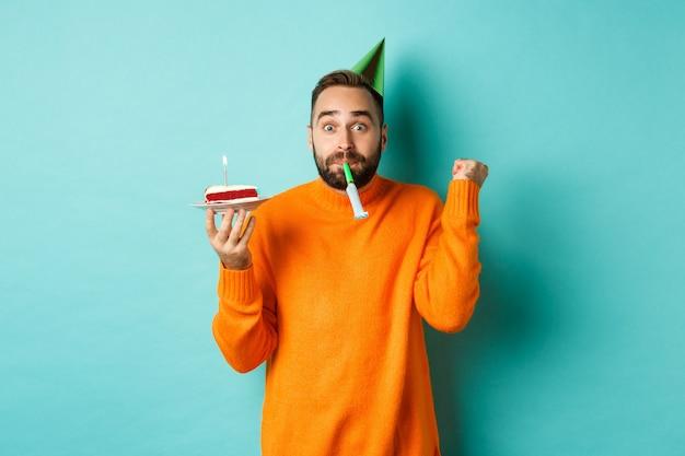 Gelukkige verjaardag jongen vieren, feestmuts dragen, wistle blazen en verjaardagstaart vasthouden en doen
