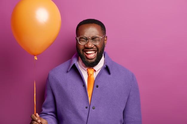 Gelukkige verjaardag kerel grinnikt naar de camera, houdt een heliumballon vast, heeft een goed humeur tijdens een feestelijke gebeurtenis, viert iets, heeft witte tanden