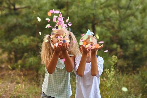 Gelukkige verjaardag kinderen met confetti op verjaardagsfeestje buiten