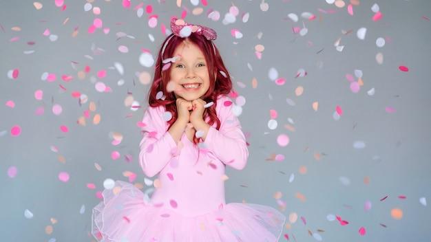 Gelukkige verjaardag meisje met confetti op grijze achtergrond