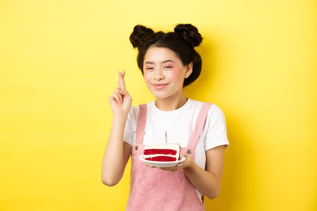 Gelukkige verjaardag meisje met glamour make-up, wens doen en vieren, kruisvinger voor droom die uitkomt, staande met cake op geel.