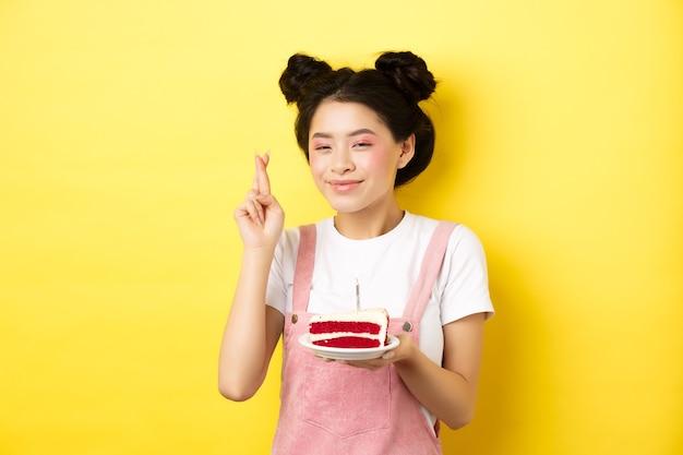 Gelukkige verjaardag meisje met glamour make-up, wens maken en vieren, kruisvinger voor droom die uitkomt, staande met cake op gele achtergrond