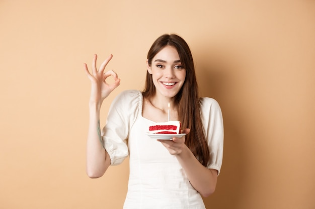 Gelukkige verjaardag meisje toon oke gebaar en houd verjaardagstaart, wens op haar vakantie, staande op beige.