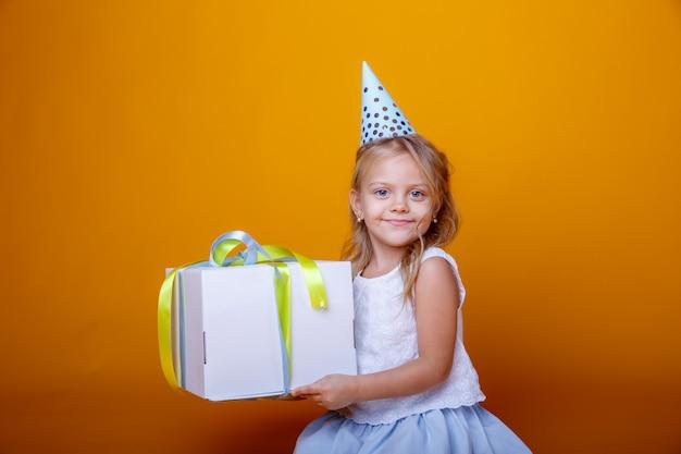 Gelukkige verjaardag portret van een kind meisje op een gekleurde gele achtergrond met een cadeau in haar handen