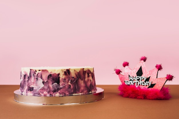 Gelukkige verjaardag roze kroon met cirkelvormige cake tegen roze achtergrond