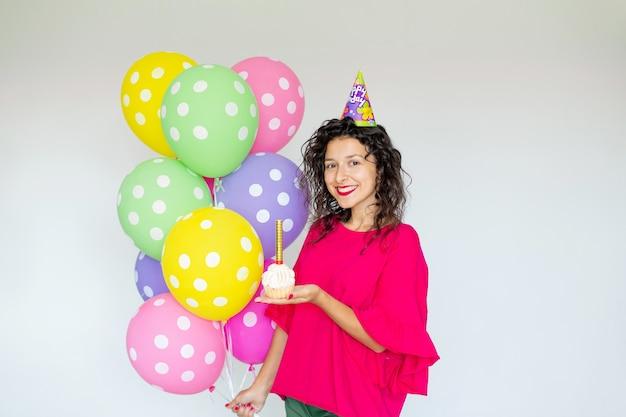 Gelukkige verjaardag. sexy brunette meisje poseren met ballonnen, vuurwerk, kleurrijke ballonnen en vakantie cake op een witte achtergrond.