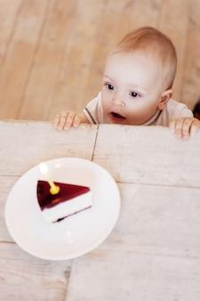 Gelukkige verjaardag voor mij! bovenaanzicht van een schattige kleine baby die naar het bord met cake kijkt en de mond openhoudt