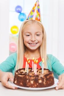 Gelukkige verjaardag voor mij! gelukkig klein meisje dat naar de verjaardagstaart kijkt en glimlacht