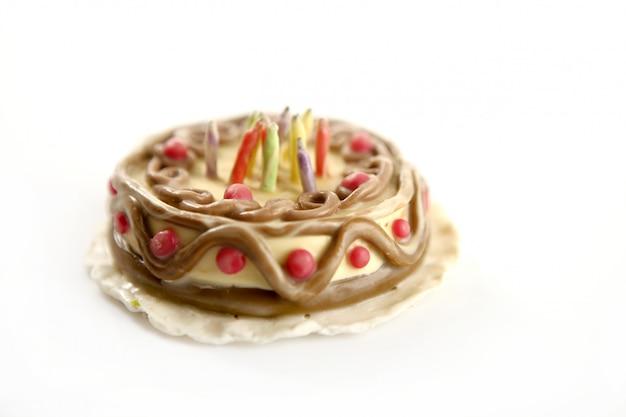 Gelukkige verjaardagscake van de plasticine van het stuk speelgoed over wit