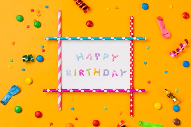 Gelukkige verjaardagsdecoratie met streamer; ballon; edelstenen en hagelslag op gele achtergrond
