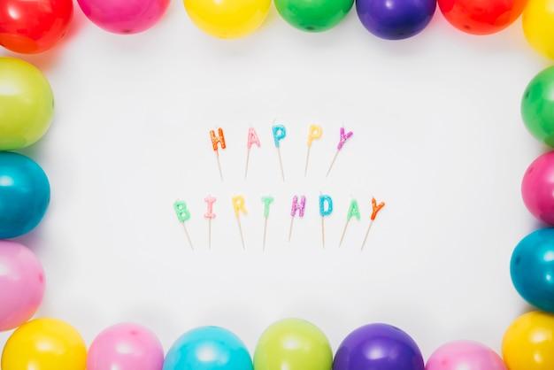 Gelukkige verjaardagskaarsen met stok op witte die achtergrond met kleurrijke ballons wordt verfraaid