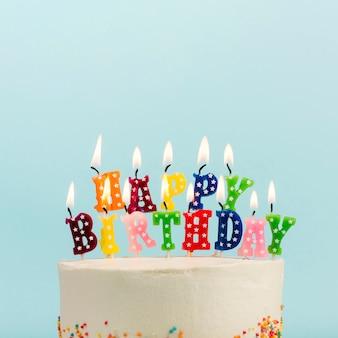 Gelukkige verjaardagskaarsen over de cake tegen blauwe achtergrond