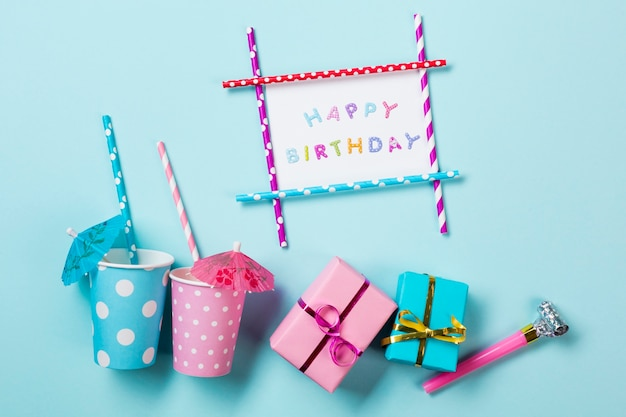 Gelukkige verjaardagskaart dichtbij de dinking glazen; geschenkdozen en blazerhoorn op blauwe achtergrond
