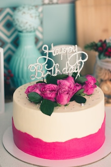 Gelukkige verjaardagstaart versierd met roze rozen