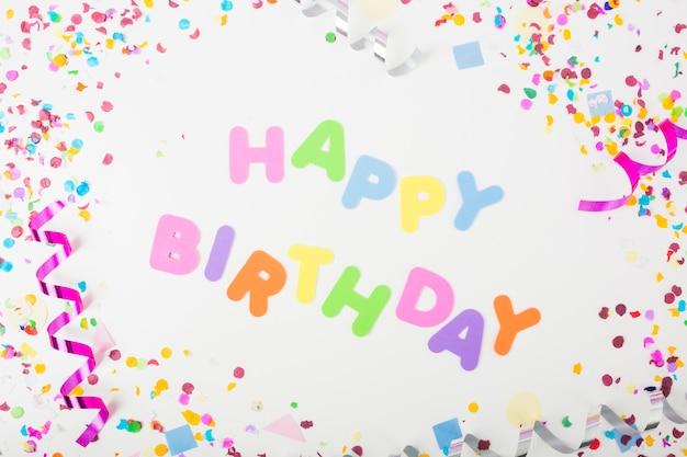 Gelukkige verjaardagstekst met confettien en krullende wimpels op witte achtergrond