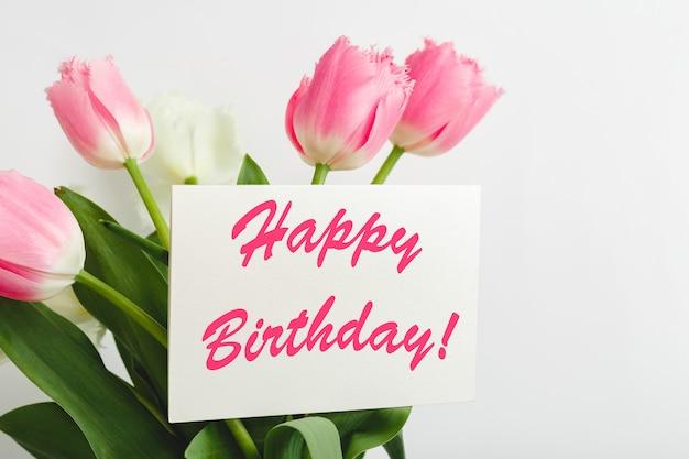 Gelukkige verjaardagstekst op geschenkenkaart in bloemboeket. mooi boeket van verse bloemen tulpen met wenskaart happy birthday op witte muur