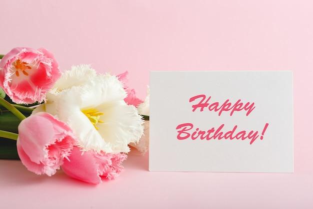 Gelukkige verjaardagstekst op geschenkenkaart in bloemboeket.