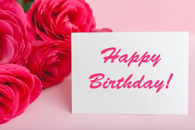 Gelukkige verjaardagstekst op kaart in bloemboeket op roze achtergrond. bloemenbezorging, felicitatiekaart. wenskaart in roze rode rozen.