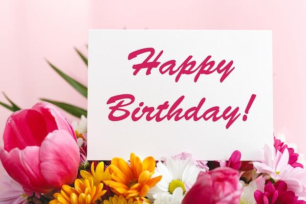 Gelukkige verjaardagstekst op kaart in bloemboeket op roze achtergrond. wenskaart in tulpen, madeliefjes, chrysant mooi lenteboeket. bloemenbezorging, felicitatiekaart.