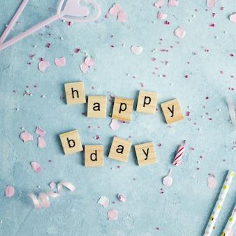 Gelukkige verjaardagswens in houten letters met kaarsen en rietjes