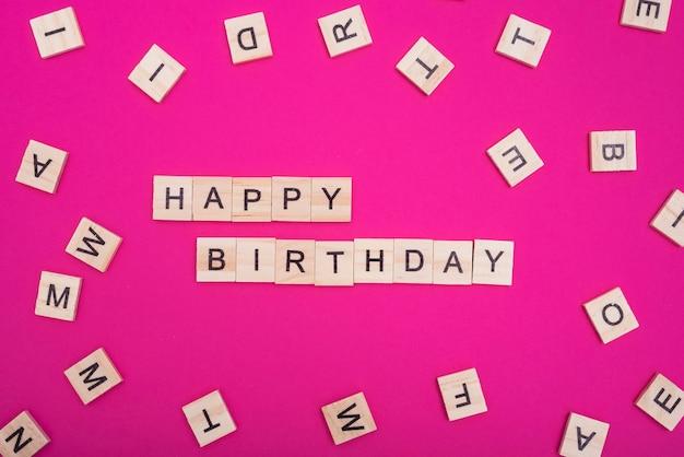 Gelukkige verjaardagswoorden op roze achtergrond