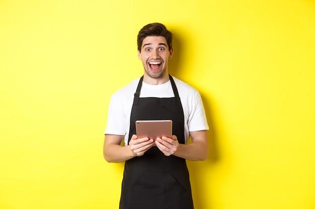 Gelukkige verkoper in zwarte schort, digitale tablet vasthoudend en verbaasd kijkend, staande tegen een gele achtergrond.