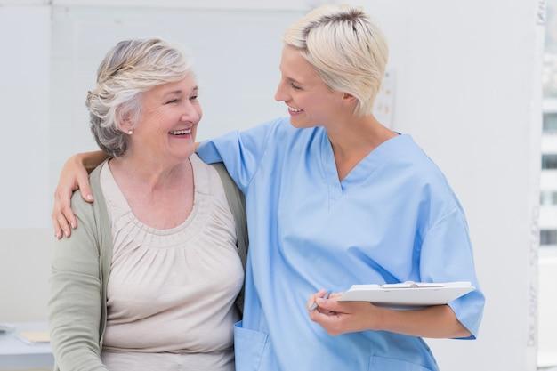 Gelukkige verpleegster met wapen rond hogere patiënt in kliniek