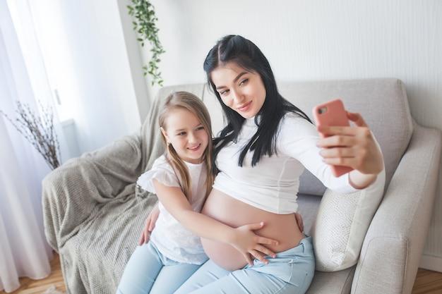Gelukkige verwachtende vrouw die selfie maakt aan haar echtgenoot. zwangere huisvrouw die op celtelefoon spreekt met haar familie.