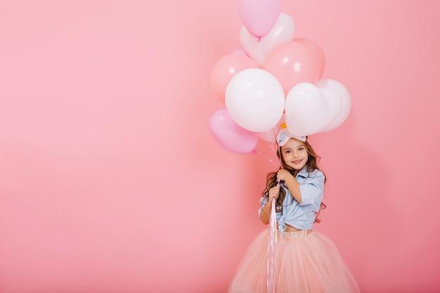 Gelukkige viering van verjaardagsfeestje met vliegende ballonnen van charmante schattig klein meisje in tulle rok glimlachend naar camera geïsoleerd op roze achtergrond. charmante glimlach die geluk uitdrukt. plaats voor tekst