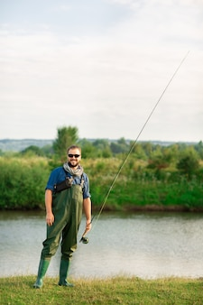 Gelukkige visser met speciaal kostuum en hengel dichtbij aan de rivier