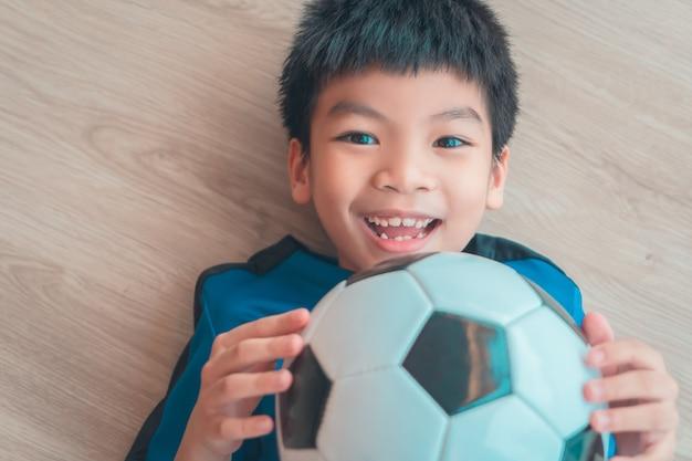 Gelukkige voetbaljongen die op houten vloer ligt die een voetbalbal met exemplaarruimte houdt.