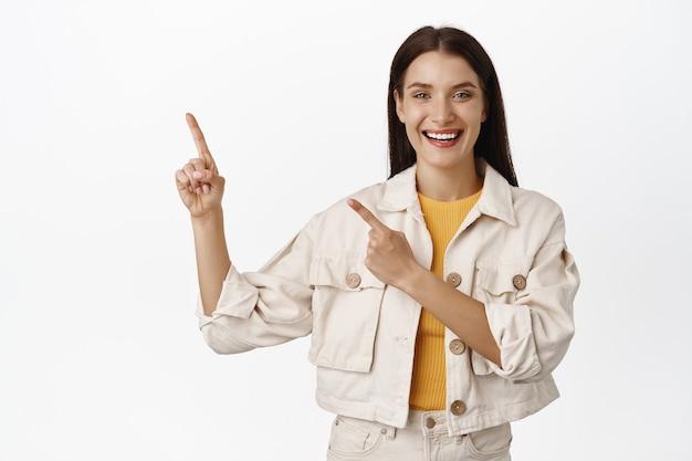 Gelukkige volwassen brunette vrouw die met de vingers wijst naar de verkoop in de linkerbovenhoek, met advertentie, banner of logo van het bedrijf, staande op wit.