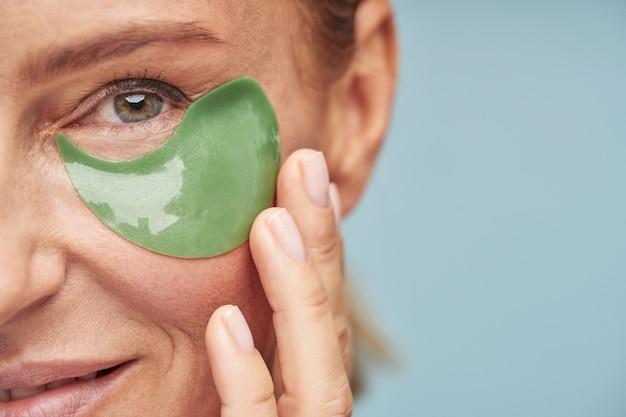 Gelukkige volwassen dame die naar de camera kijkt en geniet van de huidverzorgingsprocedure