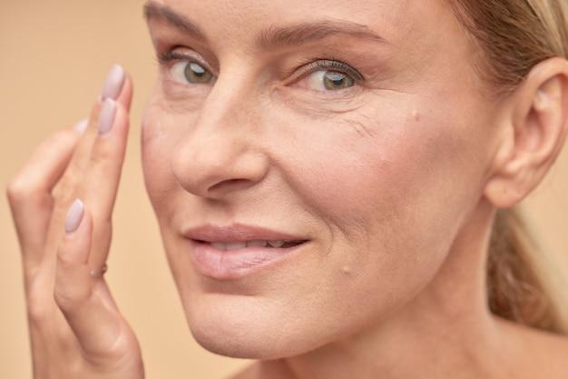 Gelukkige volwassen dame die voor de gezondheid van haar huid zorgt