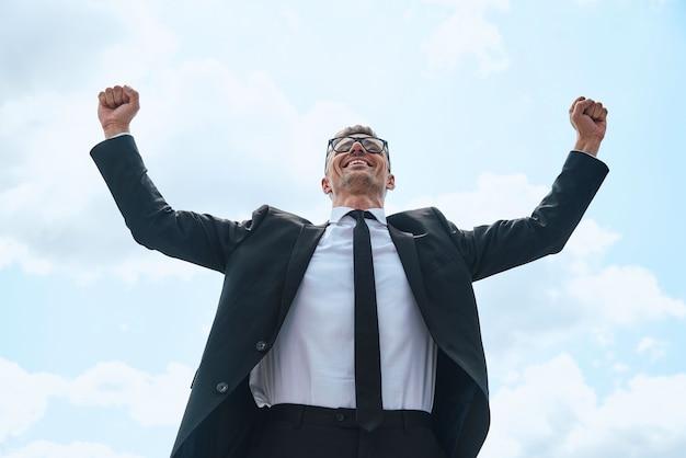 Gelukkige volwassen man in volledig pak die zijn armen omhoog houdt terwijl hij buiten voor de blauwe lucht staat
